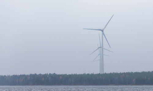 Vindkraftverk i dimma vid vattnet